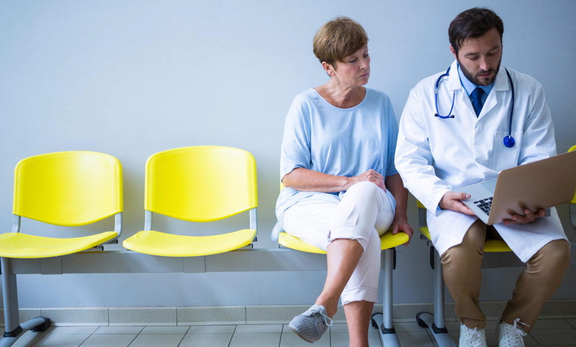 Doctor talking to woman in waiting room